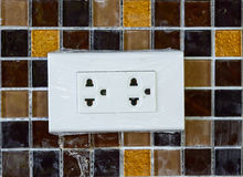 Plug socket on mosaic wall Stock Photos
