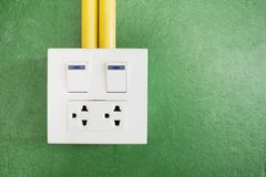 Plug and socket on wall as green background stock photography