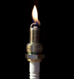 A plug spark with a flame. In a black background Royalty Free Stock Photography
