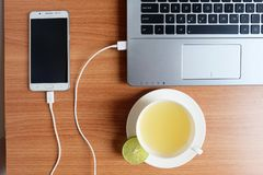 Plug in USB cord charger of the mobile phone with a laptop computer and freshly Lime juice in a white cup, on wooden floor. Top view stock photos