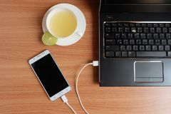 Plug in USB cord charger of the mobile phone with a laptop and freshly Lime juice in a white cup, on wooden floor. Top view stock images