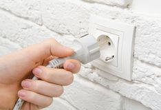 Plug the wire into the socket. On a white wall stock images
