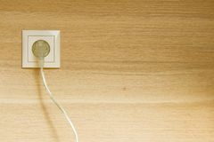 Plug in wooden wall Royalty Free Stock Photography