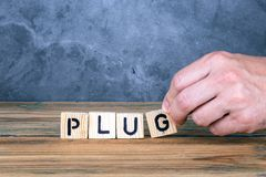Plug - word from wooden letters. On wooden table stock images