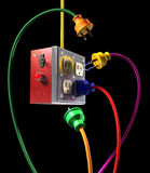 Plugged In on Black. Colorful electric plugs and socket box on a black background Royalty Free Stock Photo