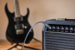 Plugged guitar and amp. Jack plugged guitar and amp close up stock photography