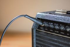 Plugged guitar and amp. Jack plugged guitar and amp close up royalty free stock photos