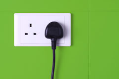 Plugged in socket against green tiles background. A electrical 3-pin plug plugged into wall socket against green tiles background Royalty Free Stock Photo