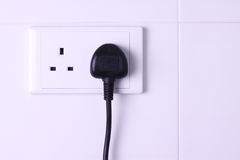Plugged in socket against white tiles background. A electrical 3-pin plug plugged into wall socket against white tiles background Stock Photos