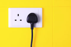 Plugged in socket against yellow tiles background. A electrical 3-pin plug plugged into wall socket against yellow tiles background Stock Photos