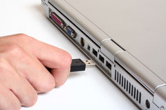 Plugging In. A usb cable being plugged in to a notebook stock image