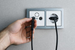 Plugging cable to outlet Royalty Free Stock Photography
