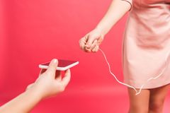 Plugging earphones into smartphone. Cropped image of mother plugging earphones, daughter holding smartphone isolated on red Stock Images