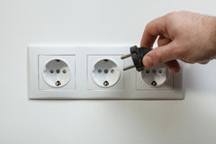 Plugging electrical cable to socket Royalty Free Stock Photography