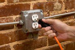 Plugging in an Extension cord. A man's hand plugging in an extension cord in  a junction box electrical outlet on a brick wall, connecting concept Stock Photos
