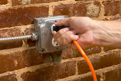 Plugging in an Extension cord. A man's hand plugging in an extension cord in  a junction box electrical outlet on a brick wall, connecting concept Stock Image