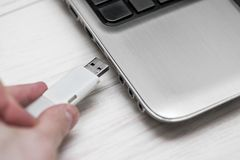 Plugging removable flash disk memory into laptop USB slot. Man hand inserting USB flash drive into laptop computer on wooden white royalty free stock image