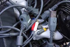 Plugs and Cables. Bunch of tangled electronic cables and game controllers Stock Image