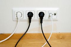 Plugs connected to the outlet in a wall Royalty Free Stock Photo