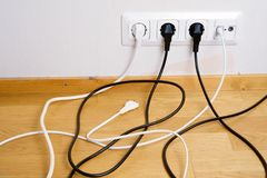 Plugs connected to the outlet in a wall Stock Images
