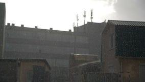 Pluie au-dessus de bas bâtiments dans le mouvement lent clips vidéos