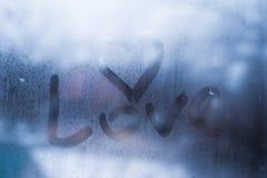 Pluie d'automne, l'inscription sur le verre en sueur - amour et coeur Photo stock