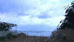 Pluie dans le pare-brise d'une voiture banque de vidéos