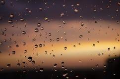 Pluie en dehors de fen?tre sur le fond du coucher du soleil Baisses de pluie sur le verre pendant la pluie Texture lumineuse des  photos libres de droits