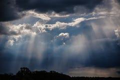 Pluie et rayons de soleil sur un ciel bleu Nuages foncés orageux Images stock