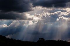 Pluie et rayons de soleil sur un ciel bleu Nuages foncés orageux Photos stock