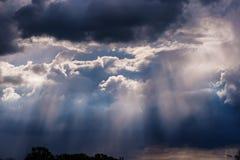 Pluie et rayons de soleil sur un ciel bleu Nuages foncés orageux Photo libre de droits