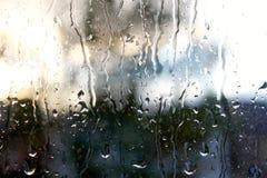 Pluie s'égouttant en bas de la fenêtre Images stock