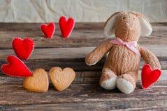 Pluizig stuk speelgoed konijntje met gevoelde harten en koekjes in de vorm van hij Royalty-vrije Stock Afbeelding