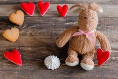 Pluizig stuk speelgoed konijntje met gevoelde harten en koekjes in de vorm van hij Stock Foto