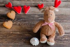 Pluizig stuk speelgoed konijntje met gevoelde harten en koekjes in de vorm van hij Royalty-vrije Stock Afbeeldingen