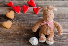 Pluizig stuk speelgoed konijntje met gevoelde harten en koekjes in de vorm van hij Stock Foto's