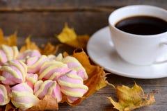 Pluizig zoet heemstsuikergoed op een plaat, een kop van koffie, gele bladeren op een houten lijst Van de dalingsontbijt of snack  Stock Fotografie