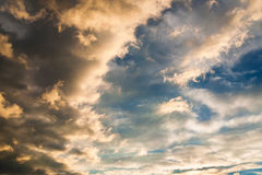 Pluizige die wolken met warm zonsonderganglicht worden verlicht Stock Foto