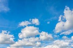 Pluizige witte wolken in een zonnige blauwe hemel Stock Foto's