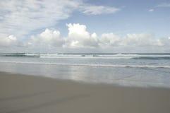 Pluizige wolken op het strand Stock Fotografie