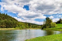 Pluizige wolken over meer in lentetijd Stock Foto