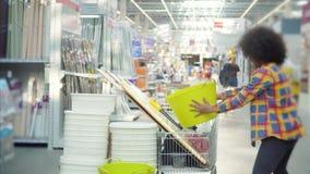 Plukt de Cheerfu Afrikaanse Amerikaanse vrouw met een afrokapsel in de winkel voor reparatie product stock videobeelden