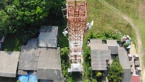 Plumón recto que vuela del top a horizontal sobre una distribución de la torre de la telecomunicación con el fondo de la naturale almacen de video
