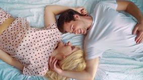 Plumón superior de los pares románticos que mienten en la cama cara a cara en direcciones opuestas almacen de video