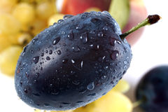 Plum. With water drops,grape and peach Royalty Free Stock Image