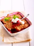 Plum and apple cobbler in a tin. With cream stock images