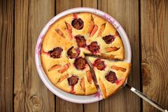 Plum and apple pie, cut, on wooden background Stock Photo