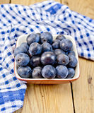 Plum blue in bowl on board with napkin Royalty Free Stock Images