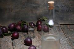 Plum brandy, bottle of Rakija. Plums brandy, Romanian tuica made of plums, wooden background royalty free stock photo