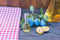 Plum brandy or schnapps with tasty  and fresh  plum fruit. And picnic cloth on vintage wood table. Copy space Stock Images